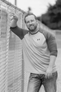 Matt Weik standing at fence black and white